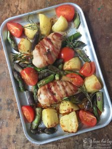 Chicken and asparagus tray bake shown in the tray by Recipes Made Easy
