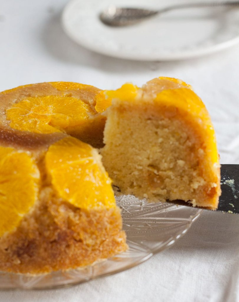 orange and stem ginger pudding with a slice being taken from it. Recipes Made Easy