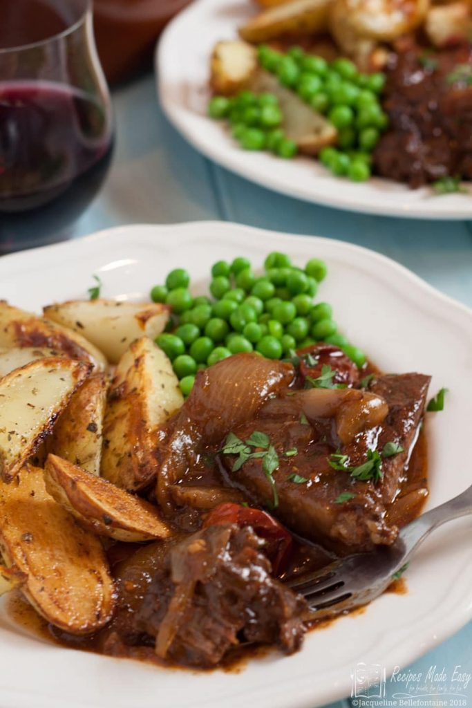 Serving of beef stifado on a plate with peas and oven chps