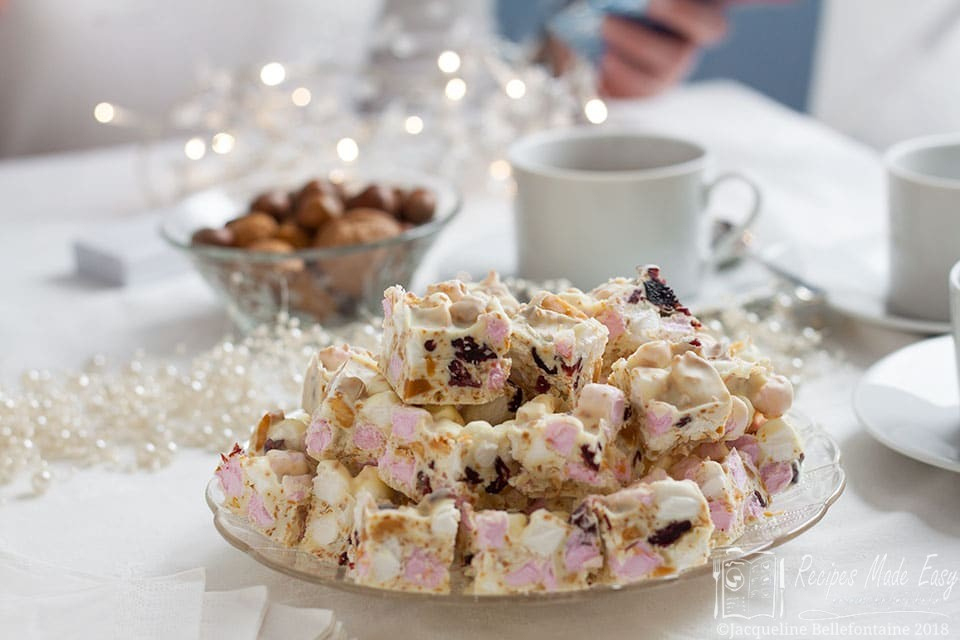 Plate of white Cristmas rocky road with coffee cup behind