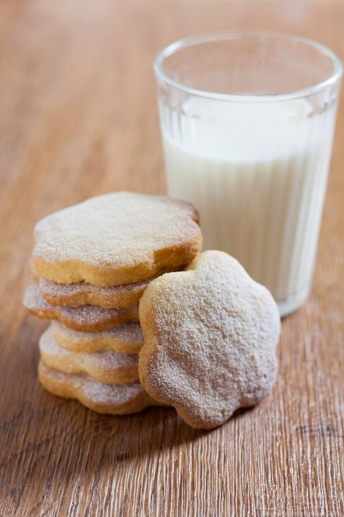 stack or orange and almond shortbreads in front of a glass of milk.