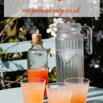 jug of water, bottle of cordial and three glasses of rhubarb cordial on a garden table