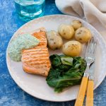 salmon with watercress sauce on a plate with vegetables