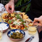 easy chicken nachos on a tray on the table, with hands picking up the tortilla chips