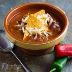 bowl of spciy mexica soup with chilli and spoon by side
