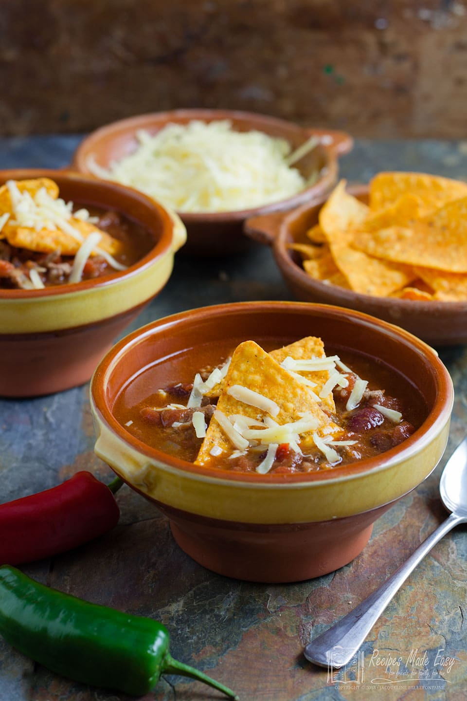 spicy mexican soup in a bowl with tortillas and cheese in background