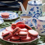 Macarons on a serving plate with tea set behind