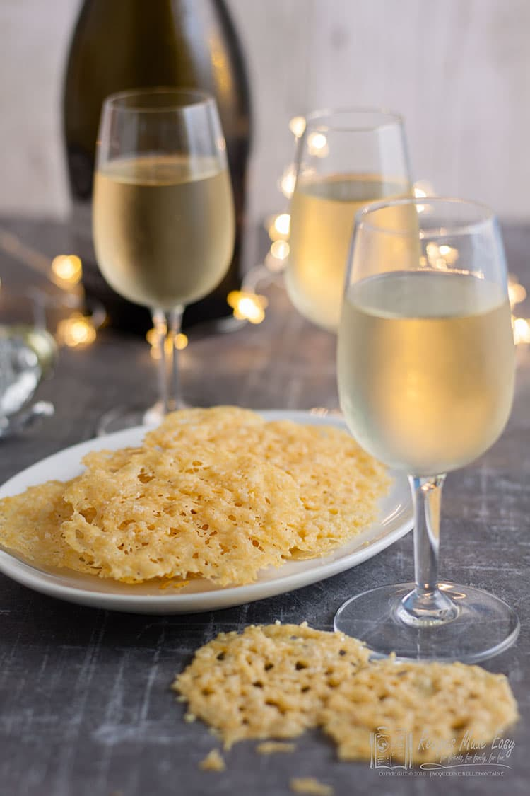 parmesan crisps on a plate with wine bottle and glasses around
