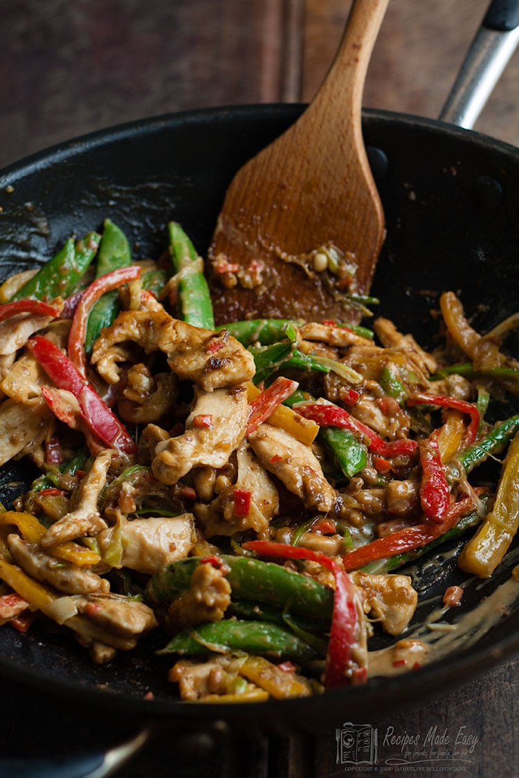 nutty chicken stir fry in a wok with wooden spoon