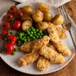 oven baked sesame chicken nuggets with roasted baby potatoes and peas on a plate.