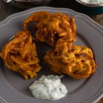 3 onion bhajis with cucumber raita on a serving plate